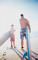 Father and Son Surfers on Beach