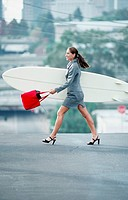 Businesswoman Carrying Surfboard on Street