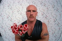 Bald Tattooed Wrestler With Bouquet