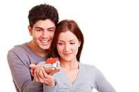 Junges Paar schaut ein Miniaturhaus auf der Hand an
