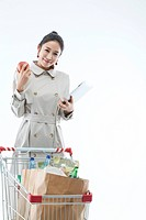 Woman With Shopping Cart Holding Digital Tablet And Apple