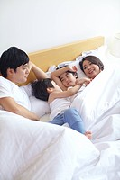 Portrait Of Happy Family On Bed