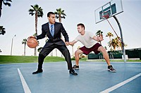 Businessman playing basketball with friend