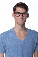 Studio portrait of young Caucasian man wearing thick glasses and looking happy on white background