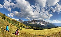 Hikers sitting near Enzianhuette mountain lodge on Plosen mountain, enjoying the view of the Afer Geisler group and Peitlerkofel mountain, Wuerzjoch r...