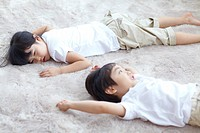 Portrait Of Boy And Girl Lying On Carpet