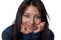 Studio portrait of Hispanic teenage girl smiling with her hands on her chin on white background