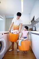 Father And Daughter With Laundry Basket