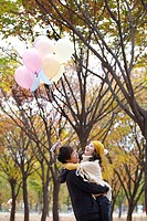 Couple Holding Balloons In A Park In Autumn
