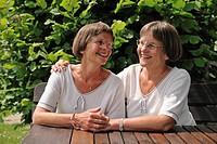 Two spry twin sisters sitting at a table in the garden