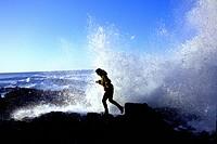 Woman Walking Along Rocks by Ocean