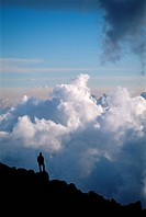 Hiker Looking Down at Clouds