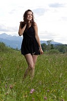 Young woman in a short black dress posing in the long grass