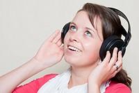 Junge braunhaarige Frau mit Kopfhörern hört mit glücklichen´ Lächeln ihr Lieblingslied