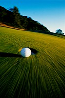 Golf Ball Rolling Toward Cup