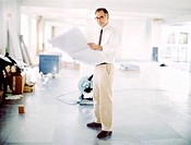 Businessman with Blueprints in Empty Room
