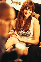 Woman Holding Drink and Socializing
