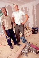 Pair of workers laying down a hardwood floor