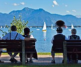 Couples wearing traditional clothes sitting on benches near harbor at lake Chiemsee, Prien, Chiemgau, Upper Bavaria, Germany