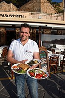Waiter serving Greek food in a restaurant at harbor, Chania, Chania Prefecture, Crete, Greece