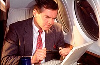 Male executive working on laptop computer in jet
