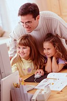 Dad and daughters at a home computer