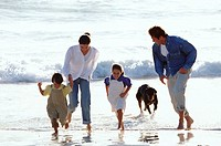 Family playing at the beach together