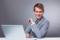 Attractive young man with a laptop on a gray background