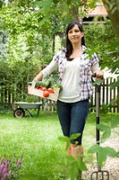 Woman carrying fresh veggies in garden