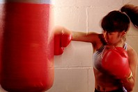 Female Boxer Practicing with Punching Bag
