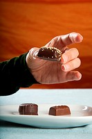 detail of woman eating brown bonbon