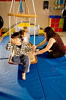 Blind and vision-impaired children ride a swing to improve their balance and body awareness in a sensory motor group at the Blind Children's Learning ...