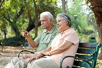 Senior man pointing at something interesting while spending time with woman at park