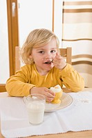 Girl eating boiled egg in breakfast, eating egg