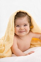 Baby girl with yellow blanket, smiling, portrait (thumbnail)