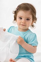 Baby girl holding napkin, smiling, portrait