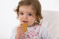 Baby girl eating cookie, close up
