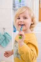 Girl brushing her teeth in bathroom, close up