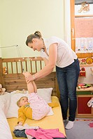 Mother holding feets of daughter in bedroom, smiling