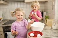 Girls preparing cake in kitchen, smiling