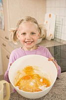 Girl holding bowl of egg yolk and flour, smiling, portrait