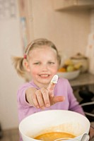 Girl showing finger covered with flour, smiling, portrait