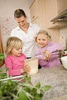 Mother and daughter pouring water into measuring cup