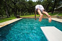 Young man, 17 years old, caucasian, jumping from diving board into swimming pool