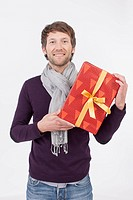 Mid adult man holding Christmas gift, smiling, portrait (thumbnail)