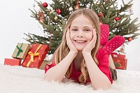 Gir lying on carpet, Christmas tree and gift in background, smiling, portrait