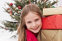 Girl holding stack of Christmas gifts, smiling, portrait