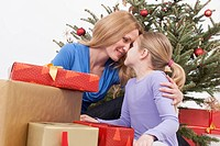 Mother and daughter with touching head, Christmas tree in background, close up