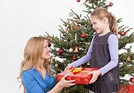 Mother giving gift to daughter, smiling