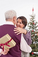 Senior man hiding gift from senior woman at christmas, smiling